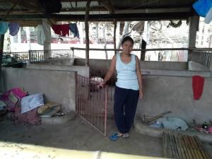 Kvinnan på bilden har flyttat in i ett grishus eftersom det klarade sig ganska bra i stormen.