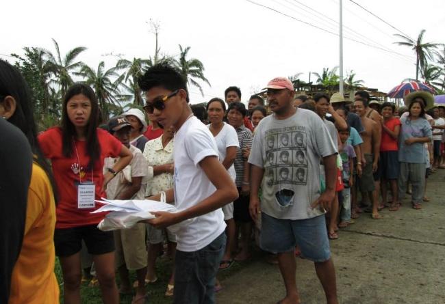 Hushållen samlas i Benabaye för att ta emot hjälpen.