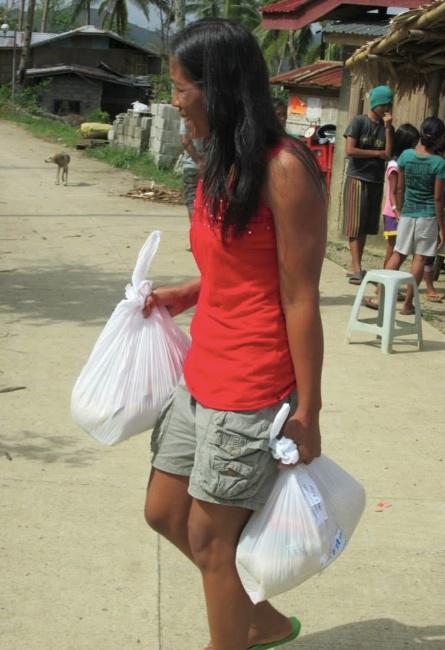En kvinna från Mahayag bär hem de matpåsar hon fått.