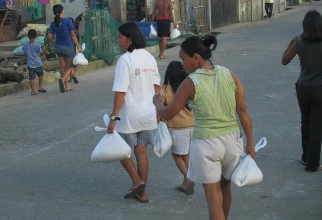 Folket i Poblacion bär hem de matkassar de har fått.