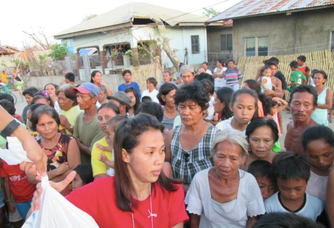 I Poblacion har folket samlats på gatan för att ta emot hjälpen.