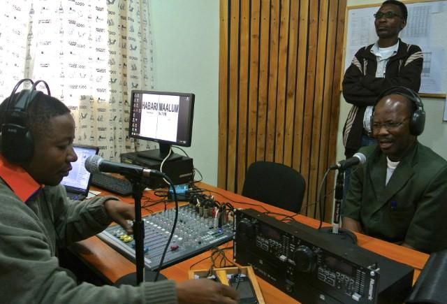 Pastor Nathanael Marandu ber och välsignar Habari Maalum FM under övervakning av HMM Administratören Amos Makiya och producent Reuben Ndaluka.