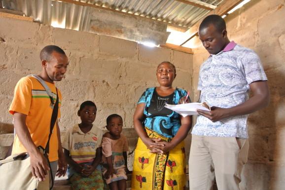 Flora Kambona har två egna barn som går i skola (9 och 10 år). Barnen på bilden är Ester (7 år) och Birgitta (4 år). Deras mamma är död. Samwel Mabula och Victor Sarenge lyssnar på vad Flora har att berätta.