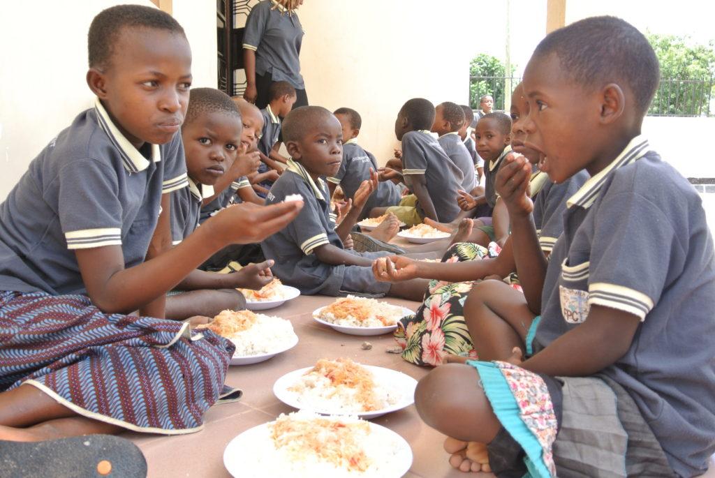 Afrikanska skolbarn sitter och äter, gör en skillnad för dem