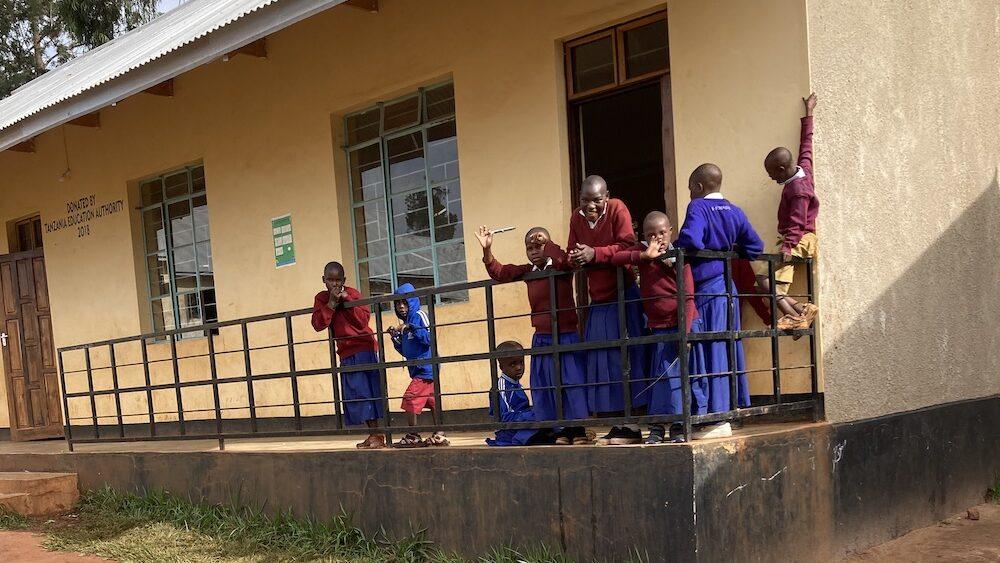 Afrikanska skolbarn som vinkar på trappa