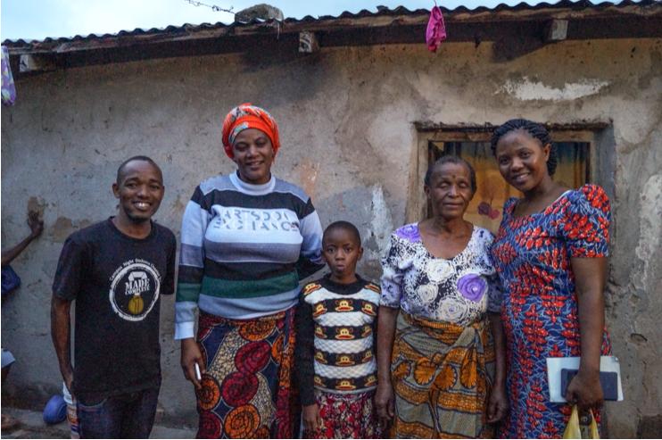 Glad afrikansk familj framför hus