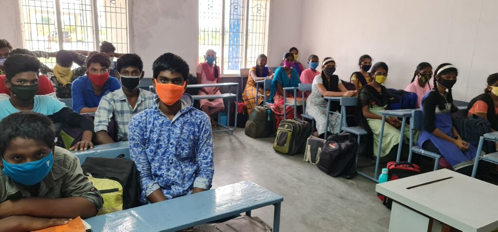 Indiska barn i klassrum iklädda skyddsmasker