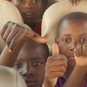 Lapsia bussissa näyttävät peukkua