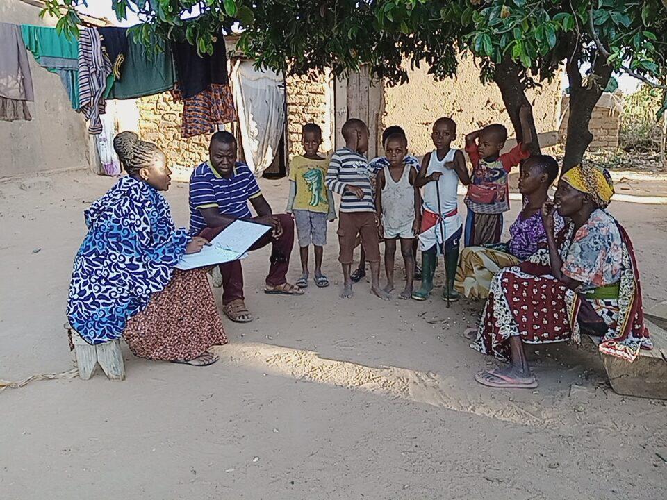 Kvinnor och barn sitter under träd