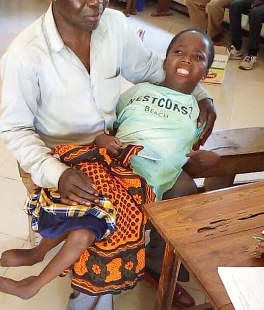 funktionsnedsatt flicka i famnen på vuxen