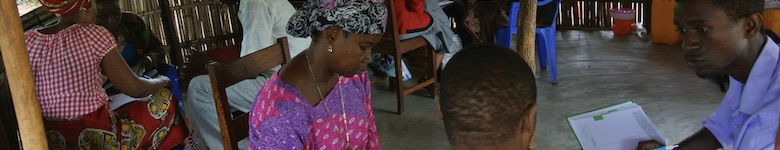 Afrikanska männikskor i hydda läser och diskuterar
